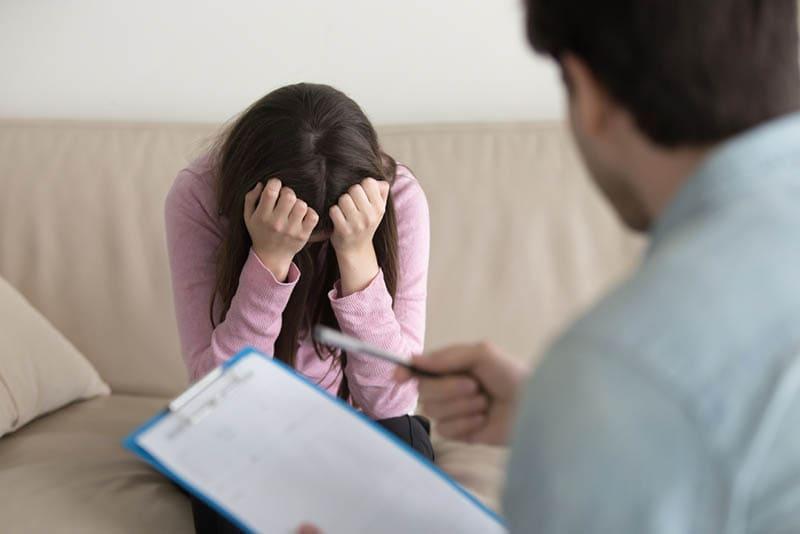 Junge Frau beim Psychologen, die sich hoffnungslos und deprimiert fühlt