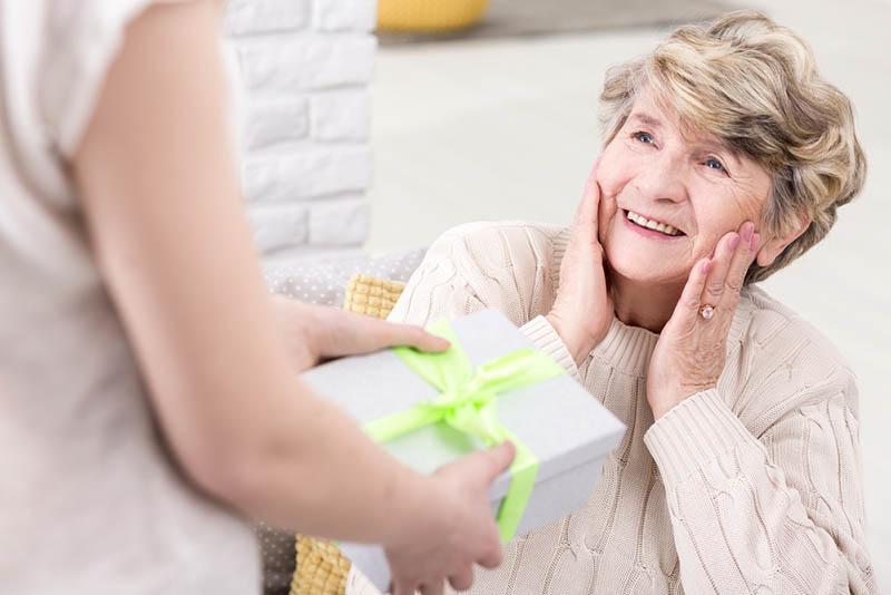 Junge Frau gibt ihrer überraschten Großmutter ein Geschenk