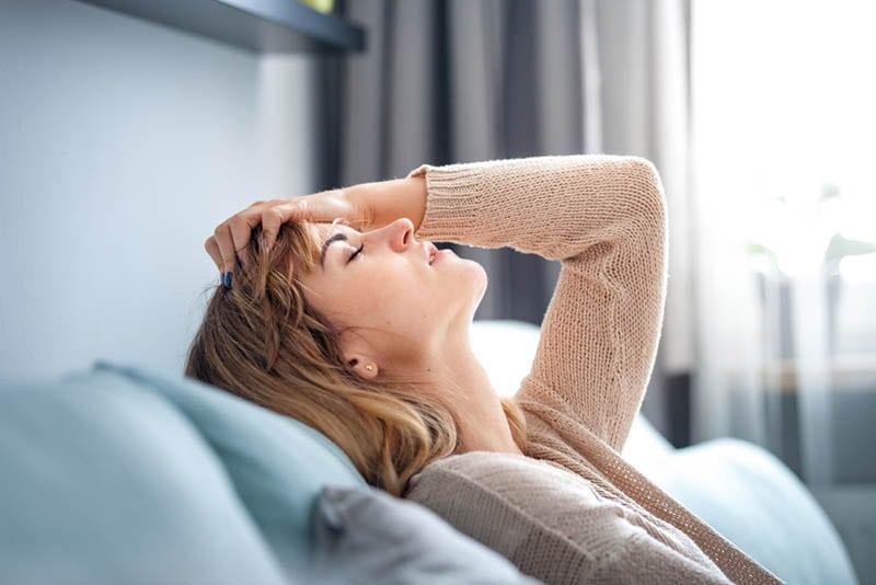 Junge gestresste Frau hält für Kopf auf der Couch