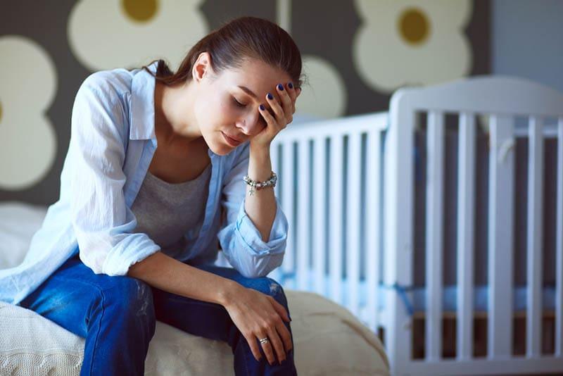 Junge müde Frau sitzt auf dem Bett in der Nähe von Kinderbetten