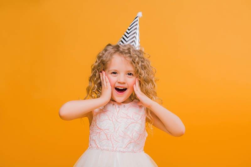 Junges schönes Mädchen trägt Geburtstagskappe
