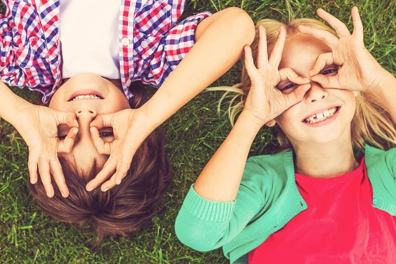 Kinder machen Grimassen, während sie auf dem grünen Gras liegen