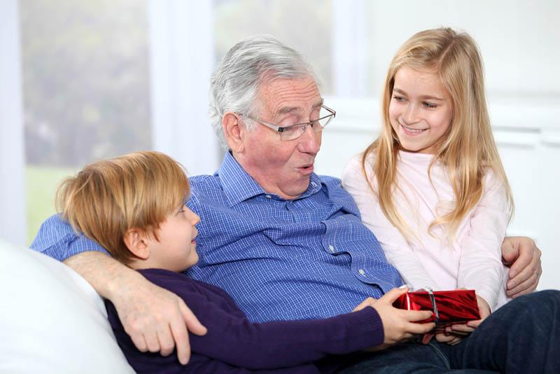 Kinder schenken ihrem Großvater ein Geburtstagsgeschenk