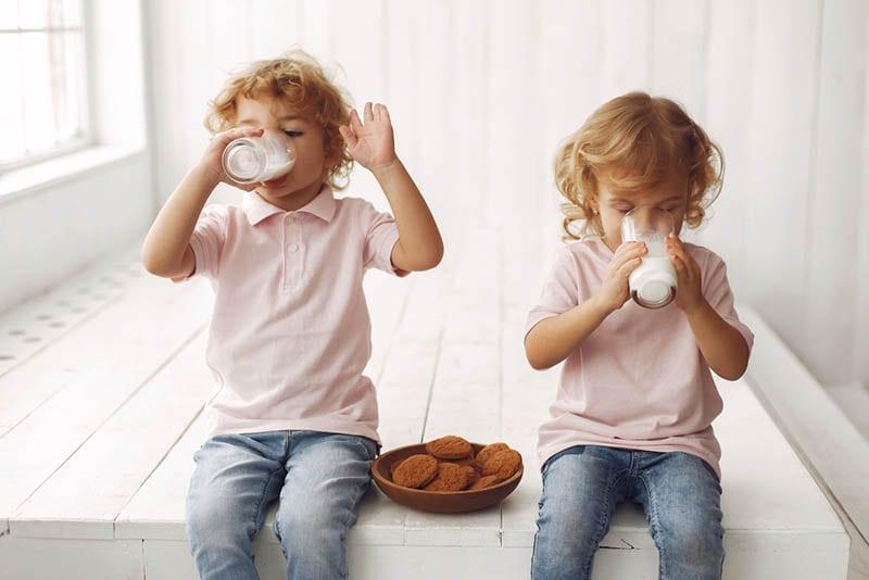 Kinder trinken eine Milch mit Keksen auf dem Teller