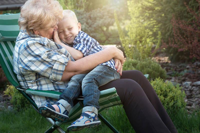 Kleiner Junge sitzt auf den Armen seiner geliebten Großmutter
