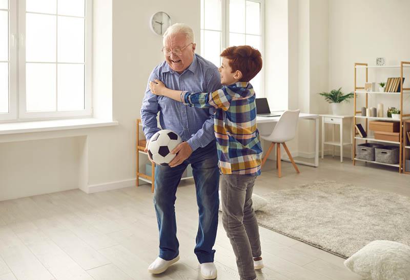Kleiner Junge und sein Großvater spielen Fußball im Wohnzimmer