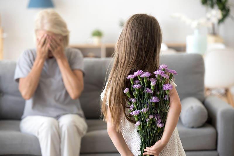Kleines Mädchen hält Blumen machen Überraschung für Großmutter