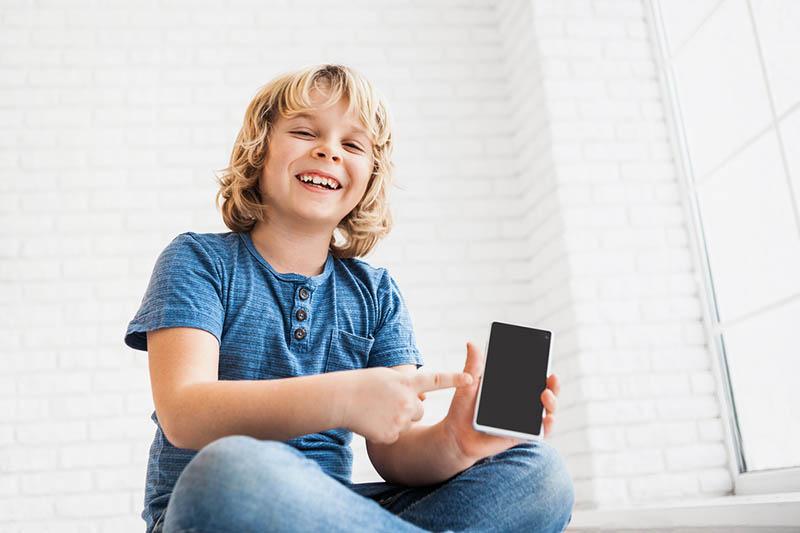 Lustiger kleiner Junge zeigt Smart Phone