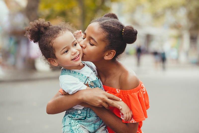 Mädchen gibt einen Kuss zu ihrer kleinen Schwester auf der Straße