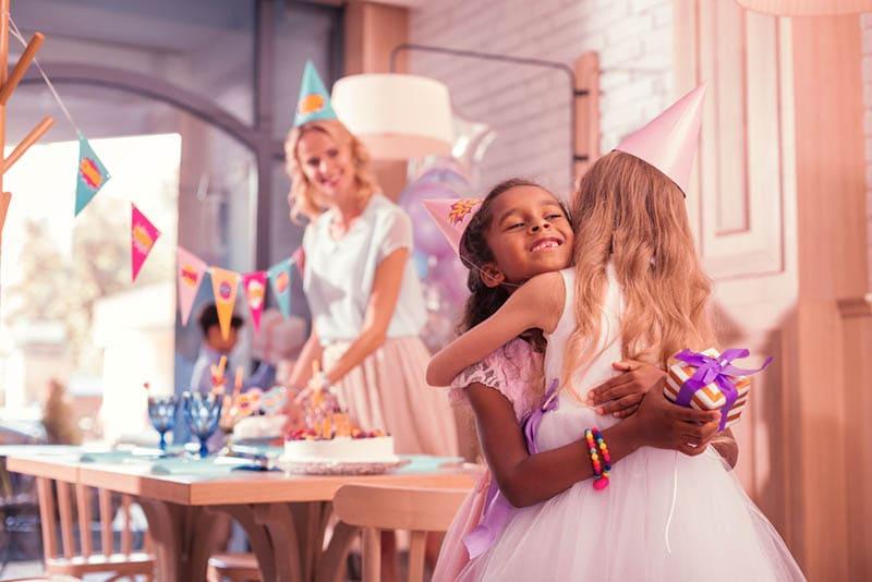 Mädchen umarmt ihre Schwester bei der Begrüßung auf der Geburtstagsparty