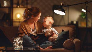 Junge Mutter liest ihrem Sohn auf der Couch ein Buch vor
