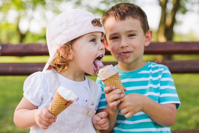 Netter kleiner Junge teilen Eis mit seiner Schwester