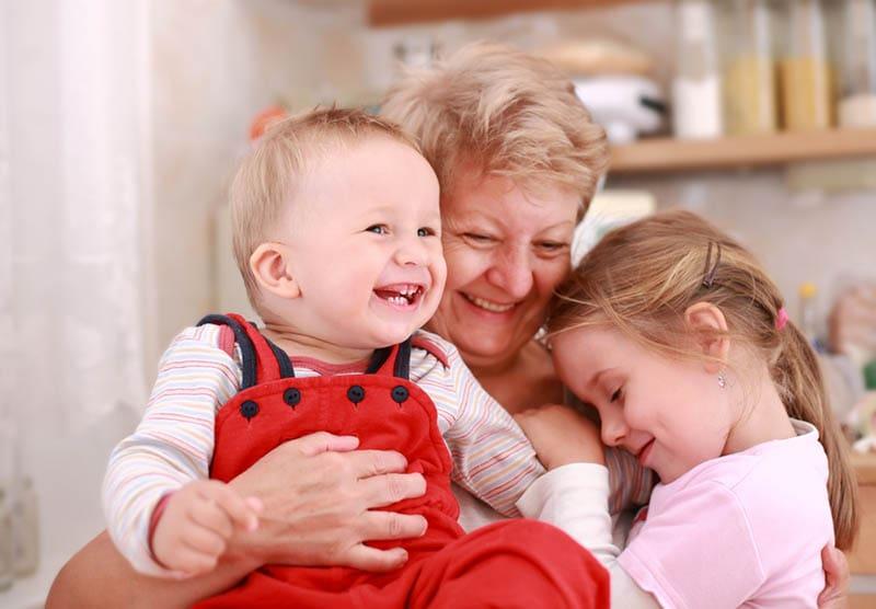 Netter kleiner Junge und kleines Mädchen glücklich mit Großmutter