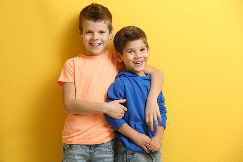 Niedliche Brüder posieren vor gelber Wand