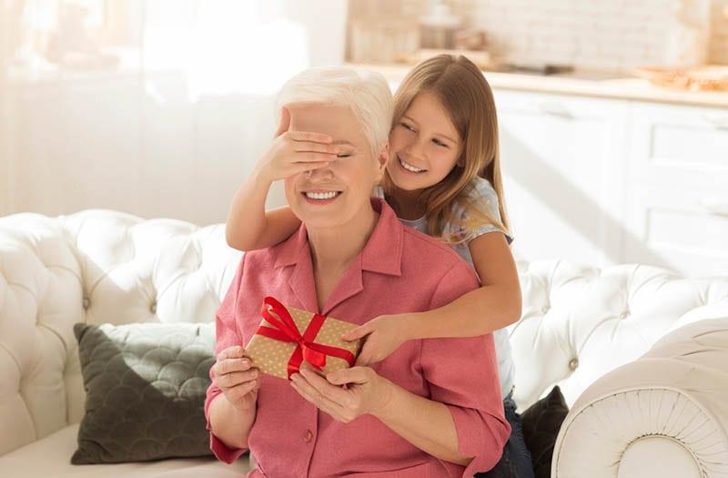 Niedliches Kind, das die Augen seiner Oma schließt, während es ein Geschenk zu Hause macht