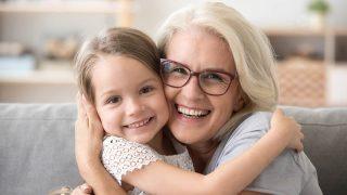 Glückliche Großmutter umarmt kleine Enkelin