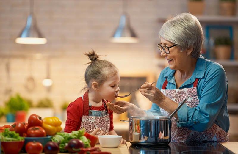 Oma füttert Enkelin in der Küche