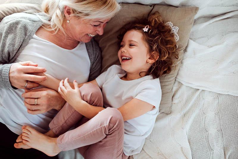 Oma und Enkelin lachen, während sie zusammen auf dem Bett liegen