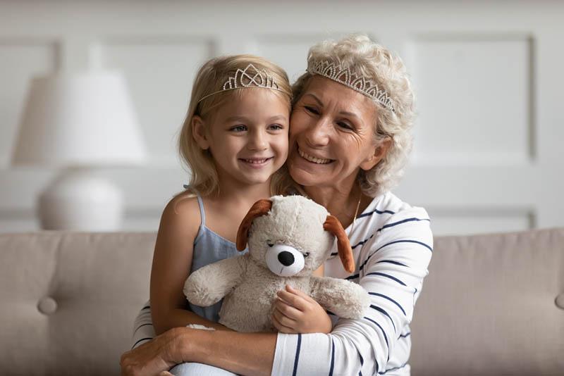 Oma und Enkelin umarmen und tragen eine Krone