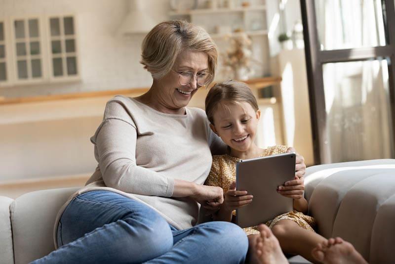 Oma und Enkelkind genießen Videoclip auf Tablet