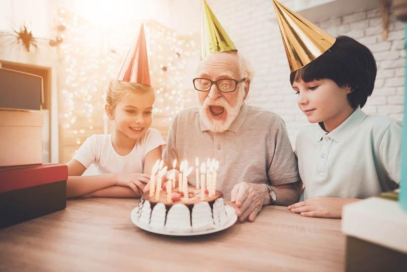 Opa bläst Kerzen auf Geburtstagskuchen mit Enkelkindern aus