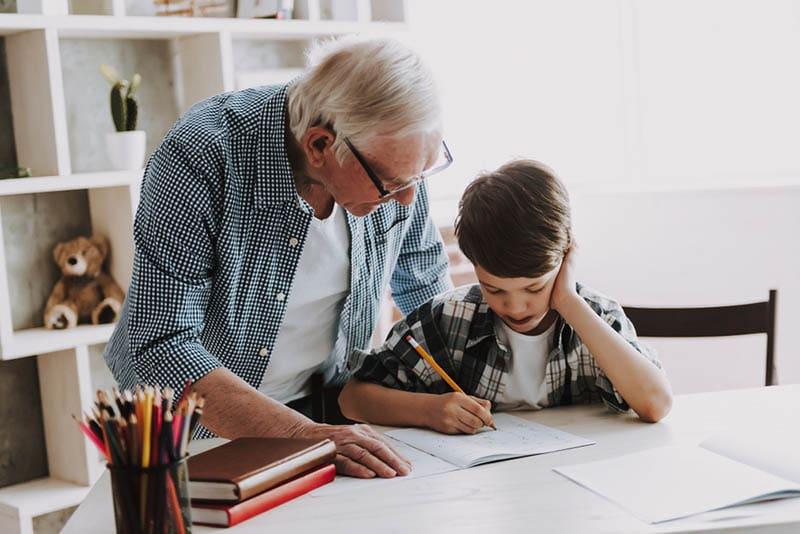Opa hilft Enkel bei den Hausaufgaben