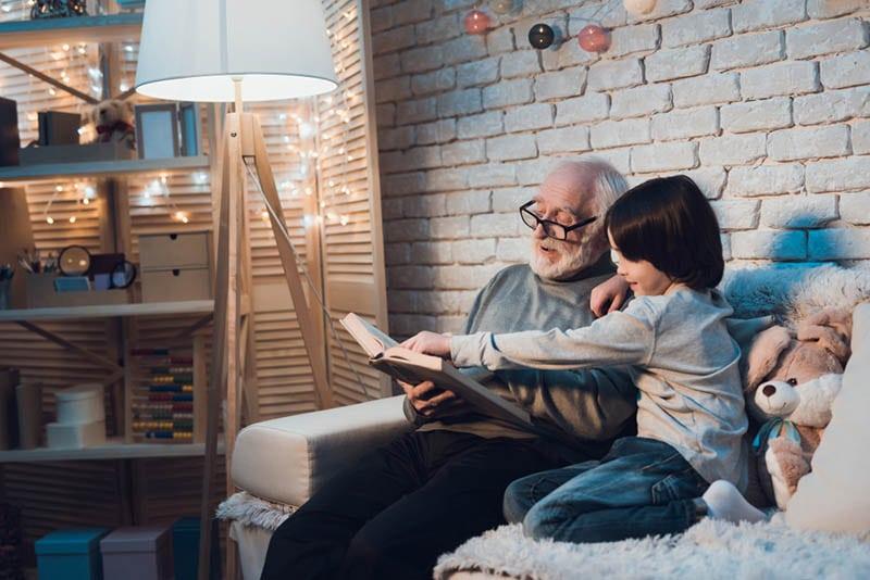 Opa liest dem Enkel zu Hause ein Märchenbuch vor