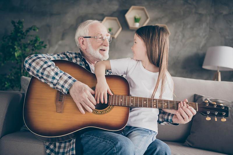 Opa spielt Gitarre mit seiner Enkelin auf der Couch