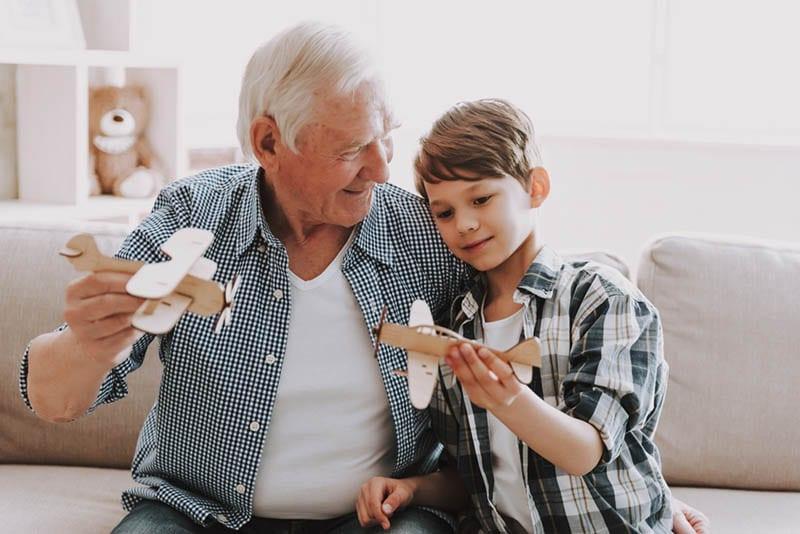 Opa und Enkel spielen mit Spielzeug auf der Couch