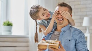 glückliches kleines Mädchen überrascht Papa mit einem Geschenk
