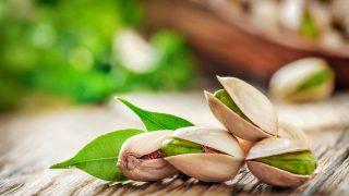 frische Pistazien auf einem Holztisch mit Blättern