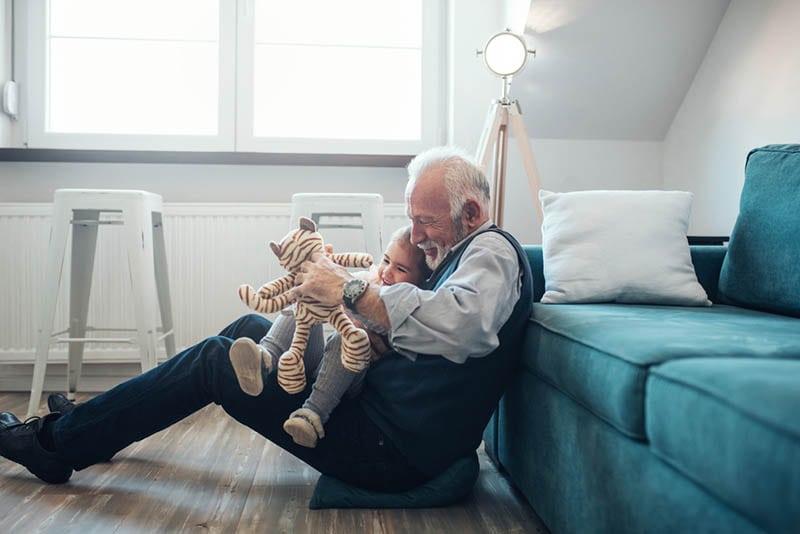 Reifer Mann spielt mit Enkelin zu Hause