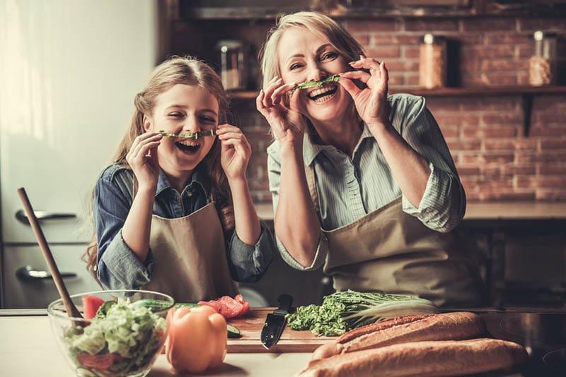 Schöne Oma und Enkelin mit Spaß in der Küche