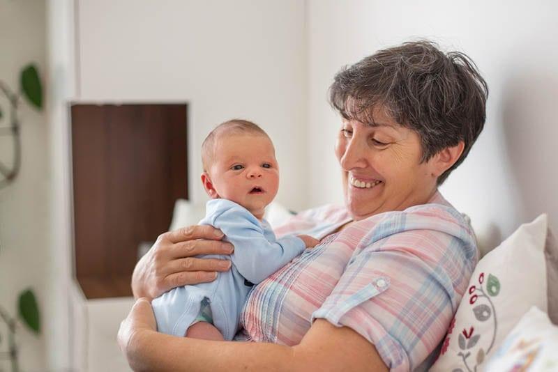 Schönes Baby Junge in Großmütter Arme zu Hause