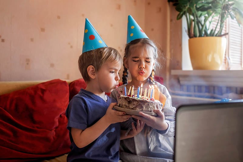 Schwester hilft ihrem Bruder beim Ausblasen von Kerzen zum Geburtstag