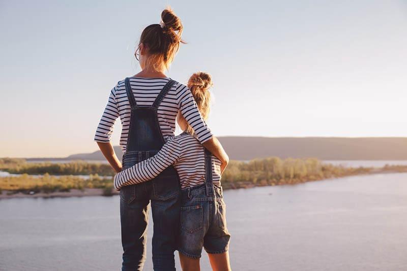 Schwestern, die sich beim Betrachten der Natur umarmen