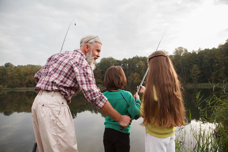 Senior Angler bringt seinen Enkeln das Angeln am See bei