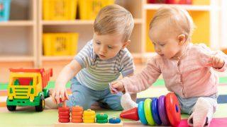 süße Babys spielen mit Spielzeug auf dem Boden