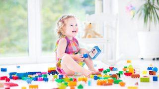 süßes kleines Mädchen spielt mit bunten Blöcken