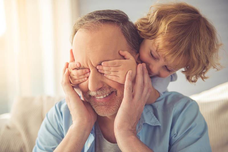 Süßer kleiner Junge bedeckt die Augen seines Großvaters und lächelt