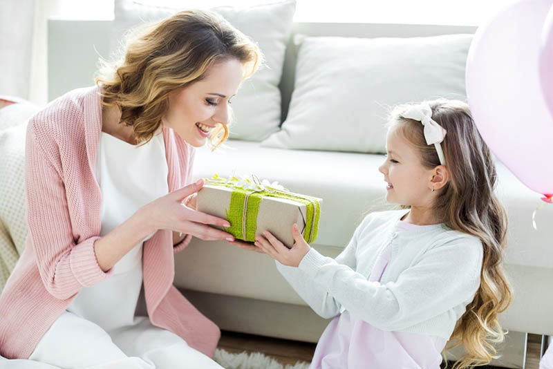 Süßes kleines Mädchen gibt Mutter ein Geschenk für Muttertag