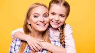ein kleines Mädchen und ihre Tante posieren vor einem gelben Hintergrund