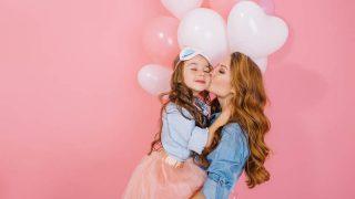 schöne Frau küsst ihr Kind auf der Geburtstagsparty