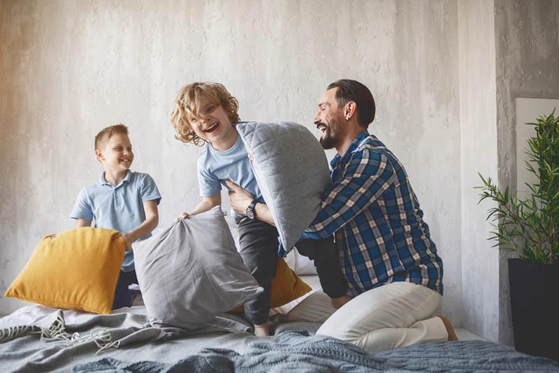 Vater spielt mit seinen Söhnen mit Kissen auf dem Bett