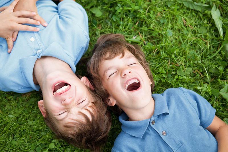 Zwei Brüder lachend auf dem Gras im Freien