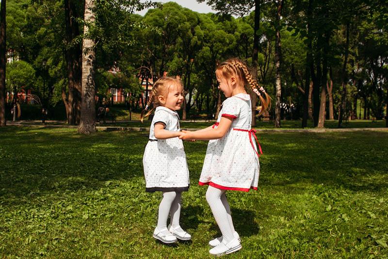 Zwei Schwestern springen händchenhaltend in den Park