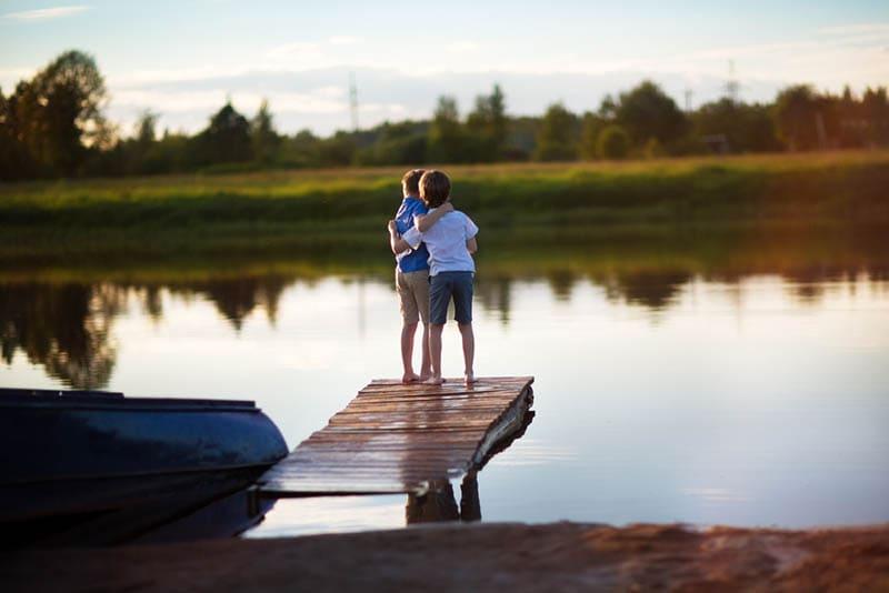 Zwei junge niedliche Jungen stehen am Flussufer