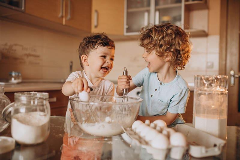 Zwei kleine Brüder backen in der Küche