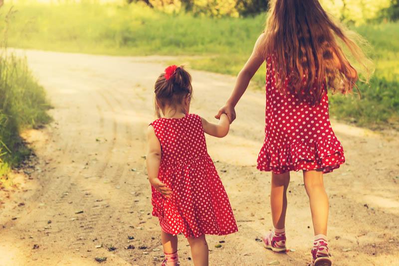 Zwei kleine Schwestern laufen auf der Straße im Park
