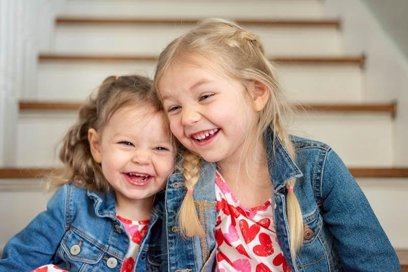Zwei süße kleine Mädchen sitzen zusammen zu Hause und lachen